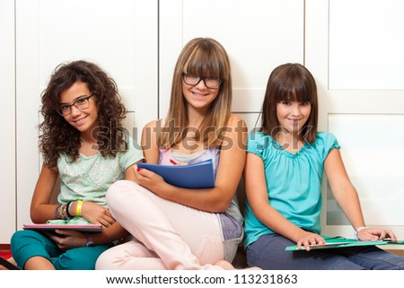 Three teenage girls sitting with files and notebooks indoors. - stock photo