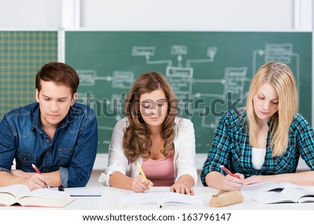 Three teenage students hard at work on their studies sitting at a desk in the classroom with their notes and textbooks spread out in front of them - stock photo