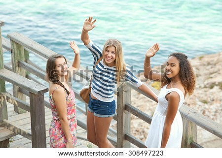 Three teenager girls arriving at beach, walking down a wooden path, turning to smile at camera and waving on a summer holiday together, beach exterior. Adolescents travel lifestyle outdoors. - stock photo