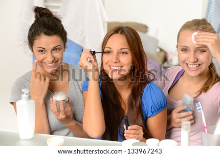 Three teenager girls enjoying getting ready in the bathroom - stock photo