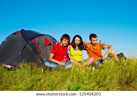Three teenagers sit beside tent - stock photo