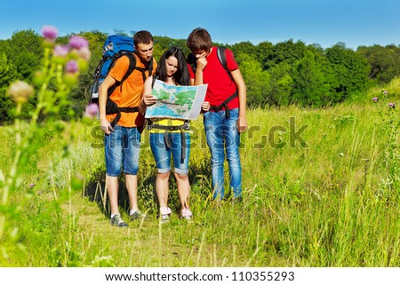 Three teenagers with backpacks looking at the tour map - stock photo