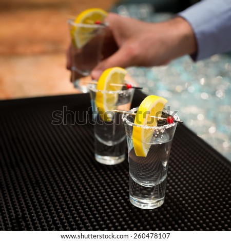Three tequila shots with lemon on a bar ribber mat. Shallow DOF and toned - stock photo