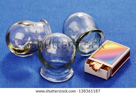 three therapeutic banks of thick glass for traditional treatment and a box of matches on a blue background. - stock photo