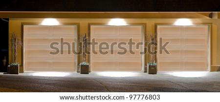 Three ( thripple ) garage doors at dawn  ( night ) time - stock photo
