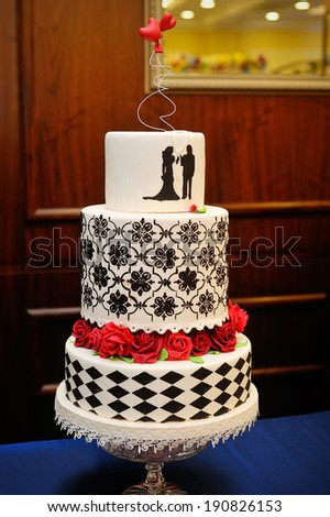 three tiered blue and white wedding cake with confectionery roses - stock photo