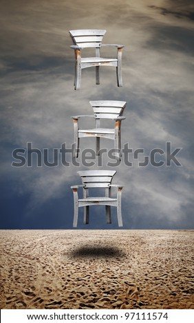 Three timber vintage beach chair levitating vertically on a desolate sandy beach against a surreal swirling cloudscape for the concept of a mysterious musical chair. - stock photo