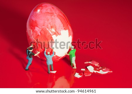 Three tiny miniature toy workmen work as a team to peel a large hard bolied egg. - stock photo