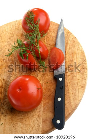 Three tomatoes and knife on a little table - stock photo