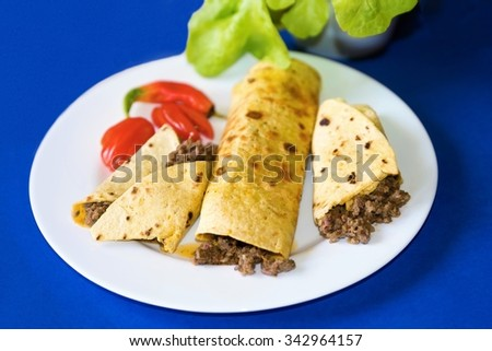 Three tortillas with minced beef and red pepper on white plate on blue background - stock photo