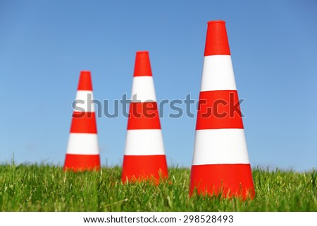 Three traffic cones on a green meadow - stock photo