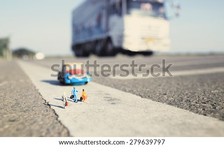 Three travelers(miniature) and a taxi on country road background. Shallow depth of field composition and vintage color. - stock photo
