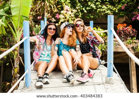 Three trendy cool hipster girls, friends, sit on the view point. Dressed in shorts, shirts and backpacks. - stock photo