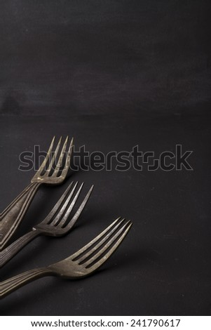 Three vintage forks on black background with text space - stock photo