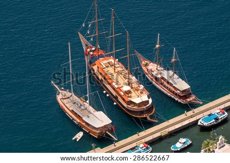 Three vintage wooden ships on Santorini island, Greece - stock photo