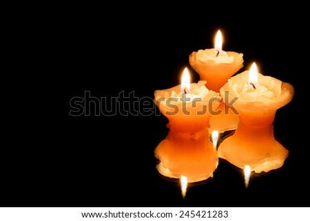 Three warm color candles rose form isolated on the black background - stock photo