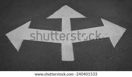 Three way arrow symbol on an asphalt road surface - stock photo