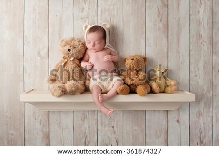Three week old newborn baby boy wearing a cream colored crocheted bear bonnet. He is sleeping on a shelf next to three Teddy Bears. Shot in the studio on a dark wood background. - stock photo