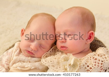 Three weeks old newborn identical twin babies dressed in lace - stock photo