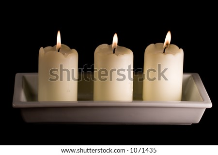 Three white candles lined up in a white saucer isolated on black - stock photo