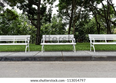 Three white chairs in the garden. - stock photo