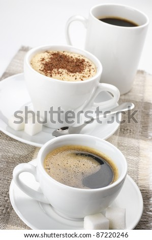 Three white cups of assorted coffee on linen napkin close-up. - stock photo