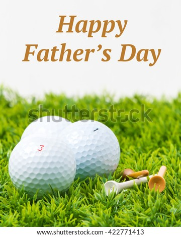 Three white golf balls and tees with a Fathers Day inscription. - stock photo