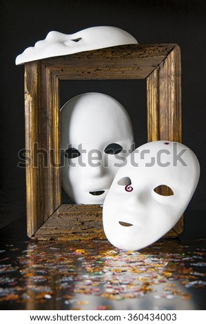Three white masks, sequins and old frame on a black background - stock photo