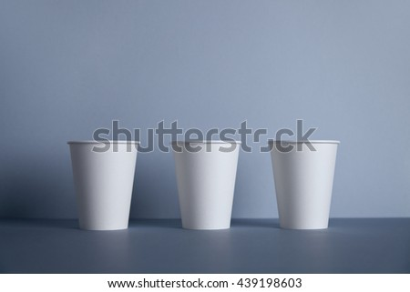 Three white paper cups in row isolated on gray - stock photo