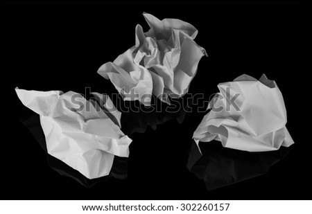 Three white scrunched up balls of waste isolated on a black background with a soft reflection. - stock photo