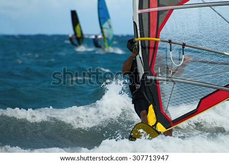 Three windsurfers in action - stock photo