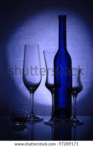 Three wineglasses, a candlestick and a bottle - stock photo