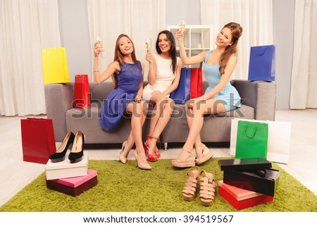 Three woman sitting at home and celebrating successful shopping - stock photo