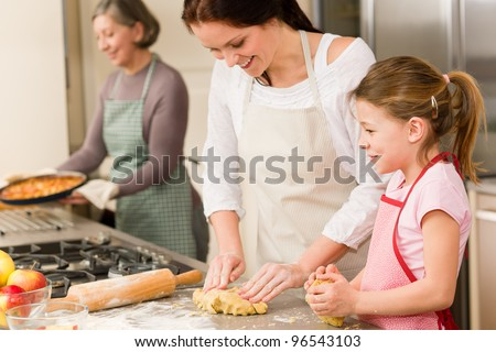Three women baking apple pies grandmother, mother and daughter - stock photo