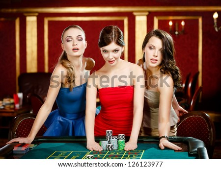 Three women bet playing roulette at the gambling house - stock photo