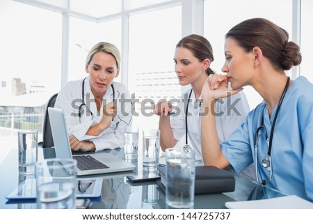 Three women doctors watching a laptop during a meeting - stock photo