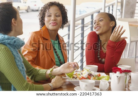 Three women eating and talking - stock photo