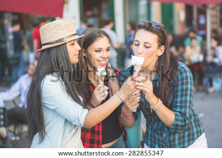 Three  women eating ice cream in the city, talking each other and smiling. This is a mixed race group, one girl is half asian and one is middle eastern. Lifestyle, friendship and urban life concepts. - stock photo