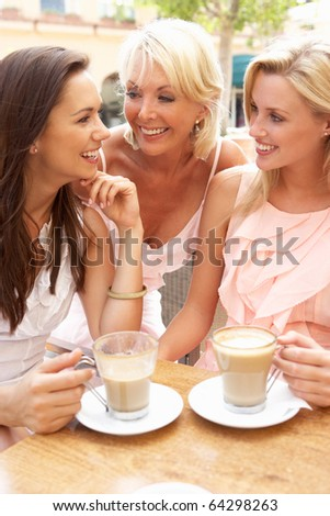 Three Women Enjoying Cup Of Coffee In Cafe - stock photo