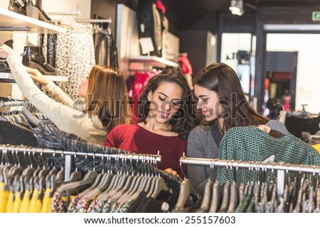 Three women in a clothing store choosing a dress. Girls are on their early twenties, they are happy about shopping, consumerism concept. - stock photo