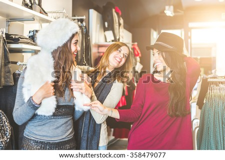 Three women in a clothing store enjoying shopping time. They are trying some hats, looking each other smiling and laughing. Friendship, lifestyle and consumerism concepts. - stock photo