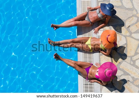 Three women in bikini wearing a straw hat by the swimming pool - stock photo