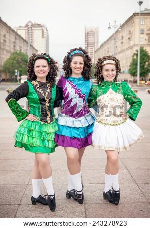 Three women in irish dance dresses and wig posing outdoor - stock photo