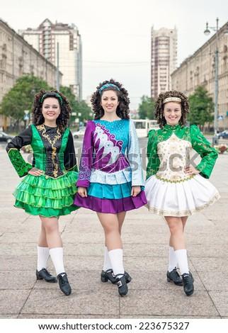 Three women in irish dance dresses posing outdoor - stock photo