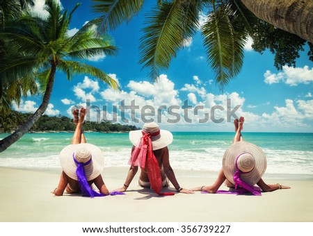 Three women in white swimsuit on the beach under the coconut tree - stock photo