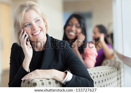 Three women on cell phones, caucasian blonde woman in foreground, smiling, sitting on couch talking on phone - stock photo