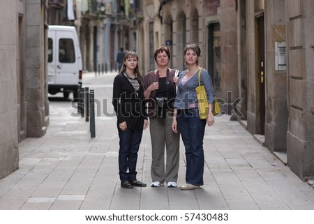 Three women poses in gothic quarter of Barcelona - stock photo