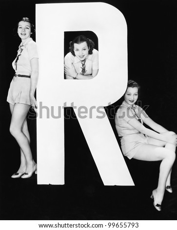 Three women posing with huge letter R - stock photo