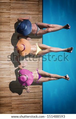 Three women reaxing on the deck by the swimming pool at exotic resort - stock photo