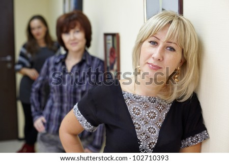 Three women stand near the wall, focus on the face of blonde - stock photo